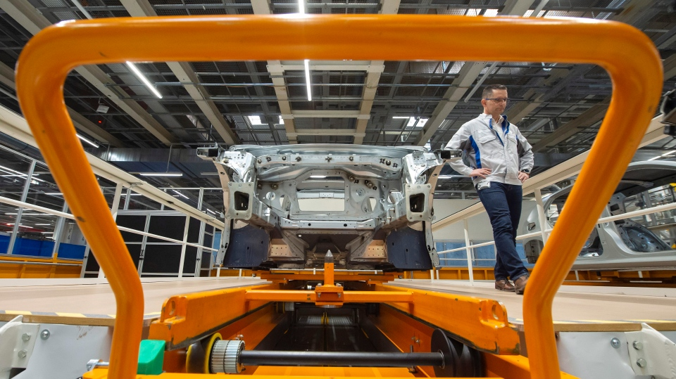 In this Tuesday, May 14, 2019 file photo, Heiko Roesch, head of body construction, walks besides the new electric 'ID.3' car body during a press tour at the plant of the German manufacturer Volkswagen AG (VW) in Zwickau, Germany. (AP Photo/Jens Meyer, File)