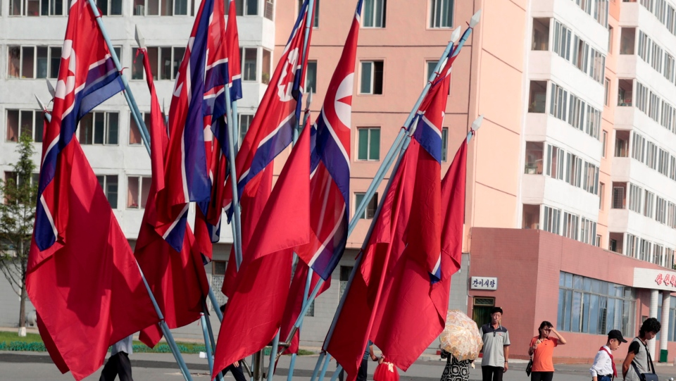 Locals walk past North Korean national flags displayed during the celebration of the 71st anniversary of the founding of the country in Pyongyang, North Korea, Monday, Sept. 9, 2019. (AP Photo/Dita Alangkara)