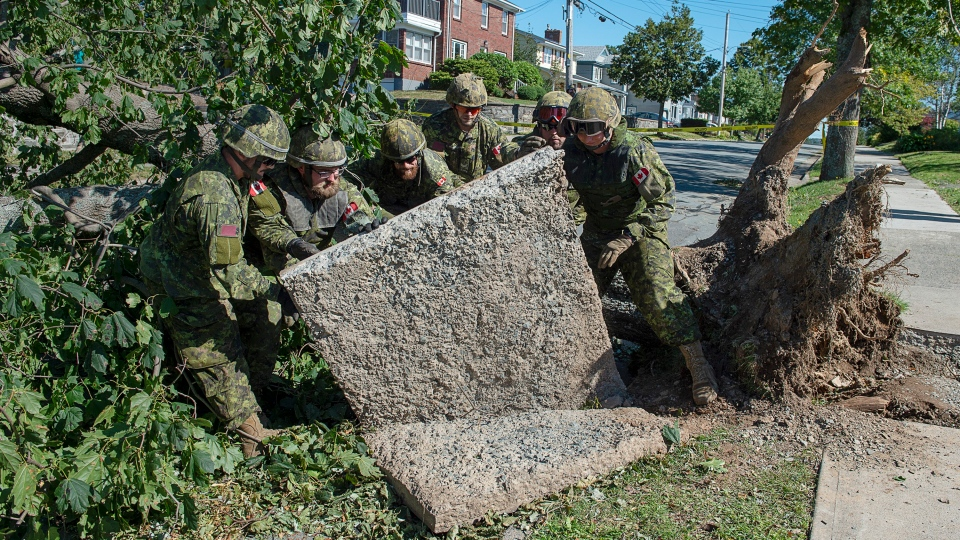 Members of the 4 Engineer Support Regiment from Canadian Forces Base Gagetown move a slab of sidewalk as they assist in the cleanup in Halifax on Monday, Sept. 9, 2019. (THE CANADIAN PRESS/Andrew Vaughan)