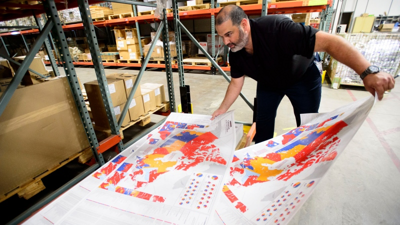 Distribution centre manager Philippe Ouellette arranges a map at the Elections Canada distribution centre in Ottawa on Thursday, Aug 29, 2019. THE CANADIAN PRESS/Sean Kilpatrick