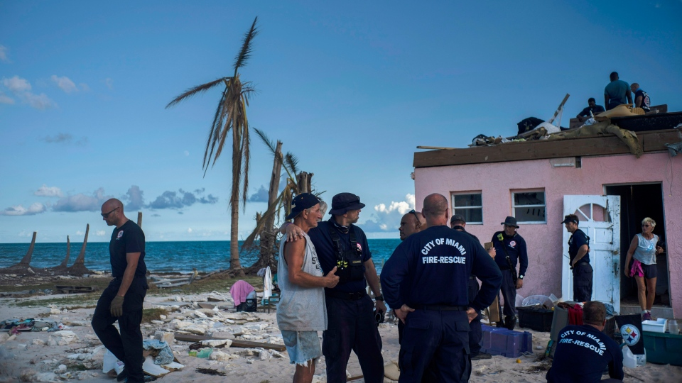 Randy Nagy, center, talks with firefighters arriving from the city of Miami to help those affected by Hurricane Dorian while his wife Silvia, 63, goes out the door of his destroyed house in Pelican Point, Grand Bahama, Bahamas, Monday, Sept. 9, 2019. (AP Photo / Ramon Espinosa)