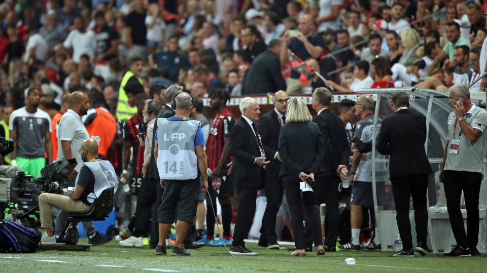 In this image taken on Wednesday, Aug. 28, 2019 players and club officials stand on the side of the pitch after the the French League One soccer match between Nice and Marseille was halted for several minutes at the Allianz Riviera stadium in Nice, southern France. The French league game between Nice and Marseille was halted for several minutes during the first half Wednesday after Nice fans unfurled two banners with homophobic messages. (AP Photo/Daniel Cole)