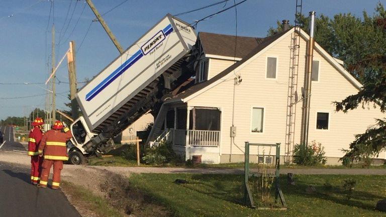 Truck flips onto house