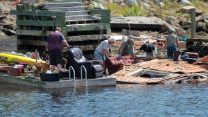 Residents recover furniture from their boat house that was swept into the waters of Herring Cove, N.S. on Tuesday, Sept. 10, 2019. (THE CANADIAN PRESS/Andrew Vaughan)