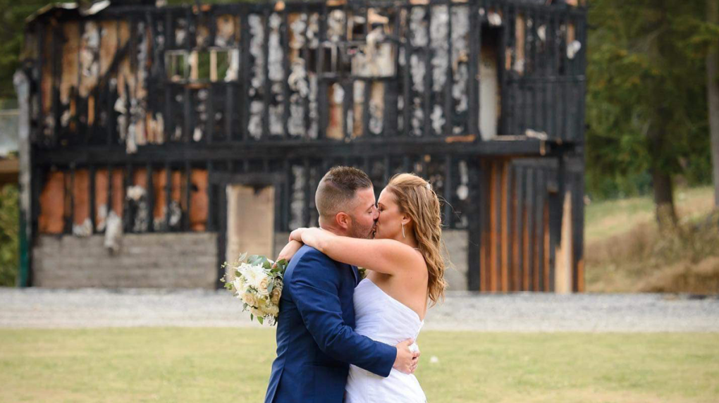 Couple poses for wedding photos in front of venue that burned days before