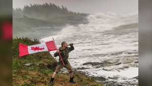 As the remnants of Hurricane Dorian barrelled towards the Maritimes, Nova Scotian and his girlfriend stuck up a 'middle finger' at the storm by snapping a dramatically patriotic photo of him overlooking the windswept coast while holding a beer and a Canadian flag. (Logan White and Katelyn Wynne)