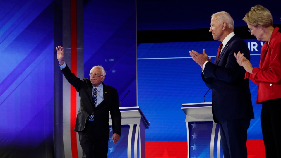 Sen. Bernie Sanders, I-Vt., left, arrives on stage as former Vice President Joe Biden, center, and Sen. Elizabeth Warren, D-Mass., right, watch as they are introduced for the Democratic presidential primary debate on the campus of Texas Southern University Thursday, Sept. 12, 2019, in Houston. (AP Photo/Eric Gay)