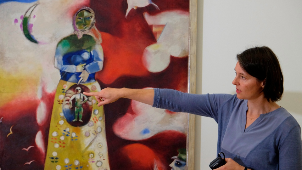 Stedelijk Museum Conservator Meta Chavannes points at Marc Chagall's painting 'The Pregnant Woman / Maternity' in Amsterdam, Friday, Sept. 13, 2019, during a presentation of results of a five-year research project into the painter. (AP Photo/Mike Corder)