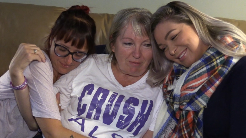 Jackie Pasch, who is living with ALS, hugs her daughters at her home in St. Thomas, Ont. on Friday, Sept. 13, 2019. (Celine Moreau / CTV London)
