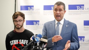 Attorney Antonio Romanucci, right, announces the filing of a civil lawsuit against e-cigarette maker Juul on behalf of his client Adam Hergenreder, left, during a news conference Friday, Sept. 13, 2019, in Chicago. (AP Photo/Charles Rex Arbogast)