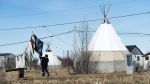 An indigenous women takes down laundry in the northern Ontario First Nations reserve in Attawapiskat, Ont., on April 19, 2016. THE CANADIAN PRESS/Nathan Denette