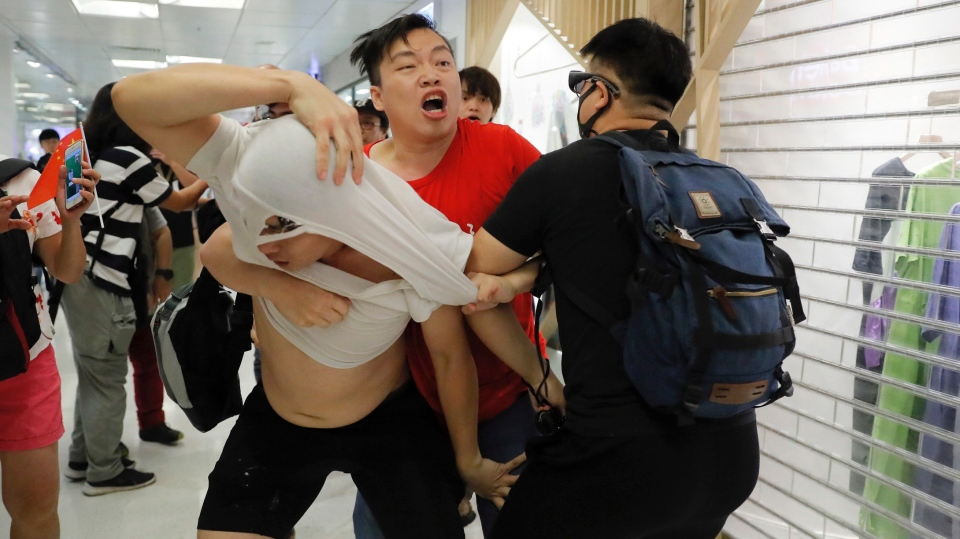 A Pro-China supporter, in red, and anti-government protesters fight at Amoy Plaza in the Kowloon Bay district in Hong Kong, Saturday, Sept. 14, 2019. (AP Photo/Kin Cheung)