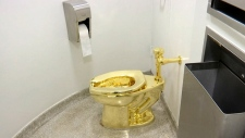 An 18-karat toilet, titled 'America,' by Maurizio Cattelan is seen in the restroom of the Solomon R. Guggenheim Museum in New York, Sept. 16, 2016.  (AP Photo, File)