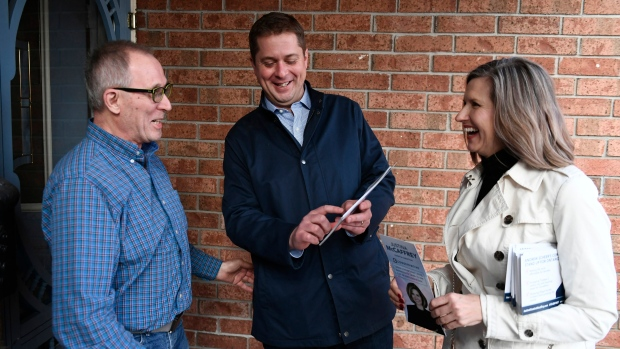 Conservative leader Andrew Scheer speaks to a resident with Kanata Carleton candidate Justina McCaffrey, right, during a door knocking event in the Kanata suburb of Ottawa in this file photo dated Thursday, April 25, 2019. THE CANADIAN PRESS/Justin Tang