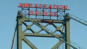 Sign hung by a climber over the Ambassador Bridge