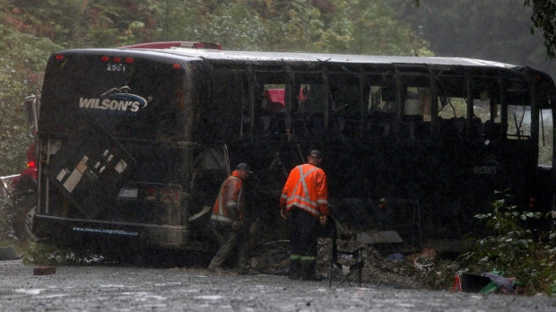 Search and rescue crews and RCMP help a tow-truck crew to remove a bus from the ditch of a logging road near Bamfield, B.C., on Saturday, September 14, 2019. THE CANADIAN PRESS/Chad Hipolito