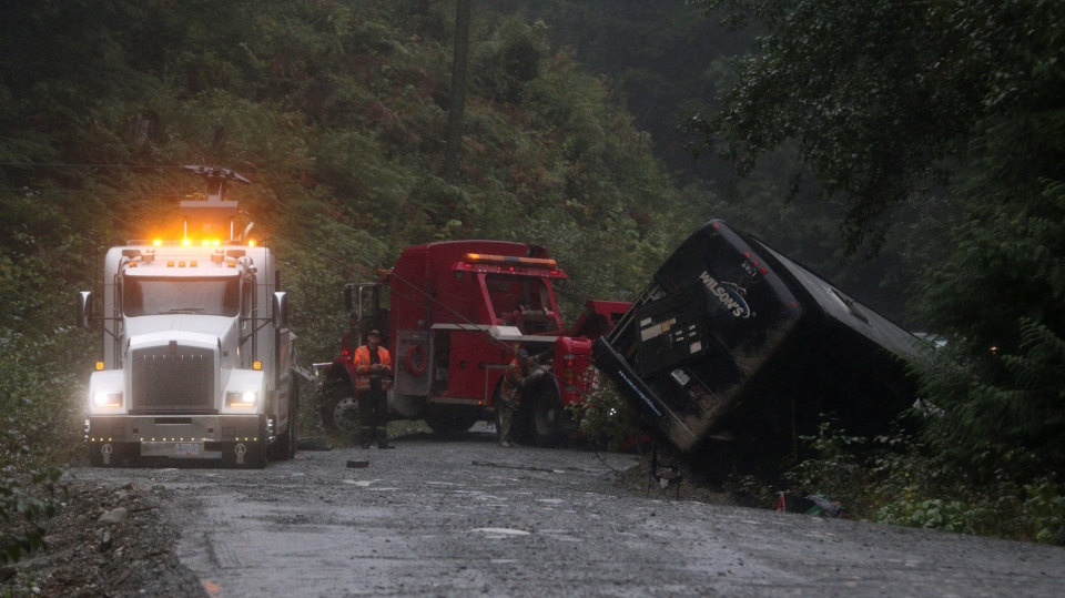 Search and rescue crews and RCMP help a tow-truck crew to remove a bus from the ditch of a logging road near Bamfield, B.C., on Saturday, September 14, 2019 THE CANADIAN PRESS/Chad Hipolito
