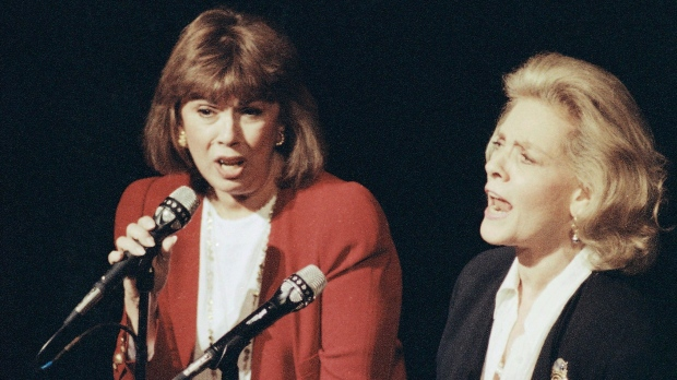 """In this Dec. 13, 1990, file photo, Phyllis Newman, left, and Lauren Bacall sing during a tribute to the late conductor Leonard Bernstein, at New York's Majestic Theatre. Newman, a Tony Award-winning Broadway veteran who became the first woman to host """"The Tonight Show"""" before turning her attention to fight for women's health, died Sunday, Sept. 15, 2019, in New York. (AP Photo/Mark Lennihan, File)"""