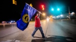 Davison resident Jeff Elkins, 37 and a GM employee who works on the line, walks across Van Slyke Road proudly waving a UAW flag as General Motors employees leave the Flint Assembly Plant at midnight as part of the national strike on Sept. 16, 2019 in Flint, Michigan. (Jake May / The Flint Journal via AP)