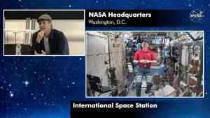 In this image taken from NASA video actor Brad Pitt, left, star of the new space movie 'Ad Astra,' speaks from NASA headquarters in Washington, to astronaut Nick Hague abroad the International Space Station, on Monday, Sept. 16, 2019. (NASA via AP)