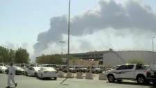 In this image made from a video broadcast on the Saudi-owned Al-Arabiya satellite news channel on Saturday, Sept. 14, 2019, a man walks through a parking lot as the smoke from a fire at the Abqaiq oil processing facility can be seen behind him in Buqyaq, Saudi Arabia. Drones launched by Yemen's Houthi rebels attacked the world's largest oil processing facility in Saudi Arabia and another major oilfield Saturday, sparking huge fires at a vulnerable chokepoint for global energy supplies. (Al-Arabiya via AP)