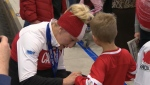 Olympic gold medallist Kaillie Humphries signs a fan's jersey at the Calgary International Airport after returning from the Sochi Winter Games in 2014