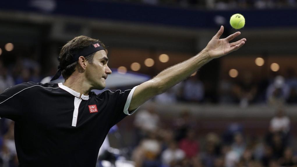 Roger Federer tosses the ball for a serve