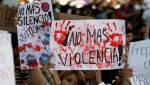 Students hold signs that read in Spanish: 'No more silence!' left, and 'No more violence!', during a protest against the murder of three film students who have become emblematic of Mexico's missing, in Guadalajara, Mexico, Thursday, April 26, 2018. (AP Photo/Eduardo Verdugo)