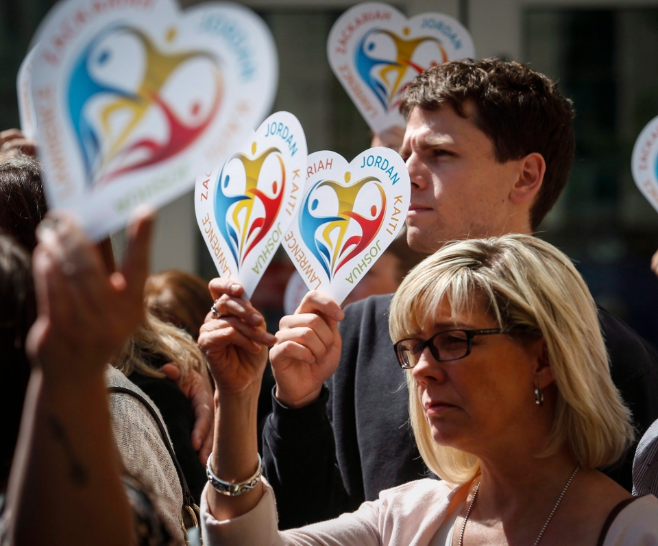 Family members of five slain students hold heart signs with their names on it following a court decision in Calgary, Alta., Wednesday, May 25, 2016. A Calgary judge found Matthew de Grood not criminally responsible on that day in the murder of five people during an end-of-school gathering at a house in April 2014. THE CANADIAN PRESS/Jeff McIntosh