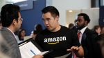 Amazon recruiter Perry Chang speaks with a prospective employee at a job fair hosted by the company Tuesday, Sept. 17, 2019, in Seattle. (AP Photo/Elaine Thompson)