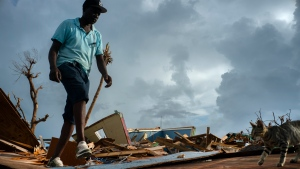 Jesner Merxius, an immigrant from Haiti, walks through the rubble in the aftermath of Hurricane Dorian in Abaco, Bahamas, Monday, Sept. 16, 2019. (AP Photo/Ramon Espinosa