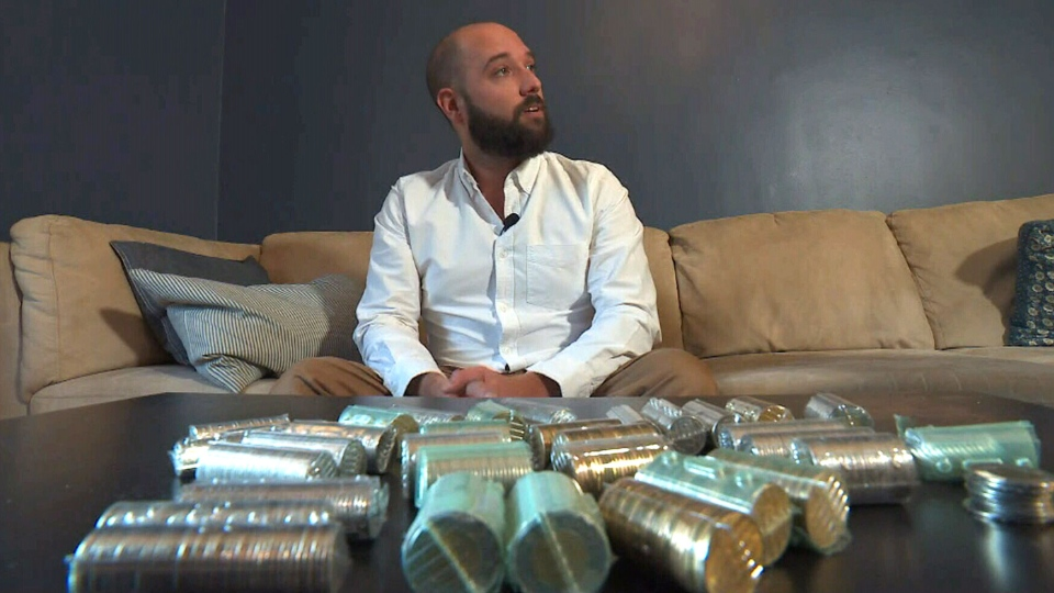 Julien Perrotte with this rolls of loonies and toonies. (CTV News Montreal)