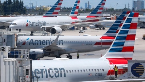 In this April 24, 2019, photo, American Airlines aircraft are shown parked at their gates at Miami International Airport in Miami. (AP Photo/Wilfredo Lee, File)