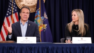 As actress Mira Sorvino watches, New York Gov. Andrew Cuomo speaks before signing a bill that increases the statute of limitations in rape cases during a bill signing ceremony in New York, Wednesday, Sept. 18, 2019. Sorvino and other actresses were there as supporters of the bill and members of the Time's Up movement, which advocates for women's rights. (AP Photo/Seth Wenig)