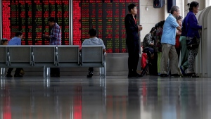 Chinese investors check stock prices at a brokerage house in Beijing, on Sept. 19, 2019. (Andy Wong / AP)