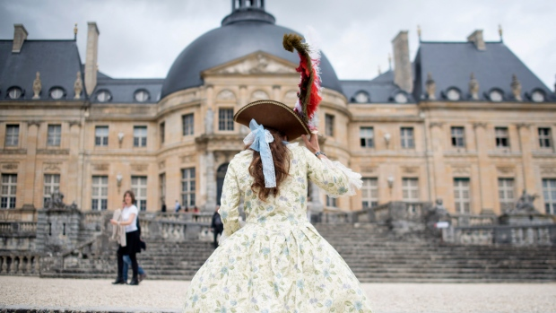 "In this July 21, 2015 file photo, a woman wearing a costume visits the Vaux-Le-Vicomte castle during the ""Great Century Day"" in Maincy, outside Paris, France. (AP Photo/Kamil Zihnioglu, File)"