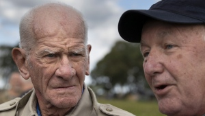 Tom Rice, a 98-year-old American WWII veteran, left, and U.S. ambassador Pete Hoekstra talks to journalists after both landed with a tandem parachute jump near Groesbeek, Netherlands, on Sept. 19, 2019. (Peter Dejong / AP)