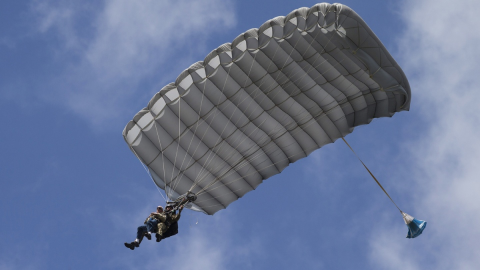 Tom Rice, front left, approaches the landing zone during a tandem parachute jump near Groesbeek, Netherlands, on Sept. 19, 2019. (Peter Dejong / AP)