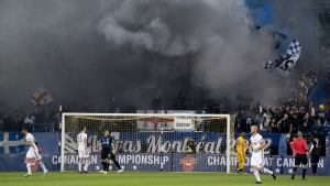 Fans blow smoke from the stands