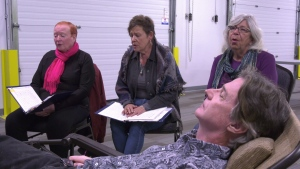 The Edmonton Chapter of Threshold Choir practices while a member lays down to experience what being on the receiving end of the service is like. Sept. 18, 2019. (CTV News Edmonton)