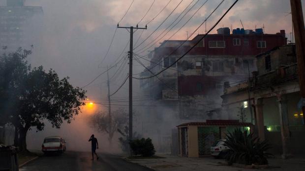 Fumigation fog fills the Vedado neighborhood after soldiers sprayed to kill mosquitos in Havana, Cuba, Tuesday, March 15, 2016. (AP Photo/Desmond Boylan)