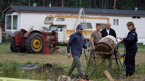 Members of the RCMP investigate a rural property on the outskirts of Prince George, B.C. Friday, August 28, 2009. (Jonathan Hayward / THE CANADIAN PRESS)