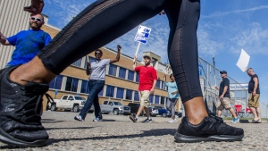 General Motors employees circle at a Flint Assembly Plant entrance, on Sept. 19, 2019. (Jake May / The Flint Journal via AP)
