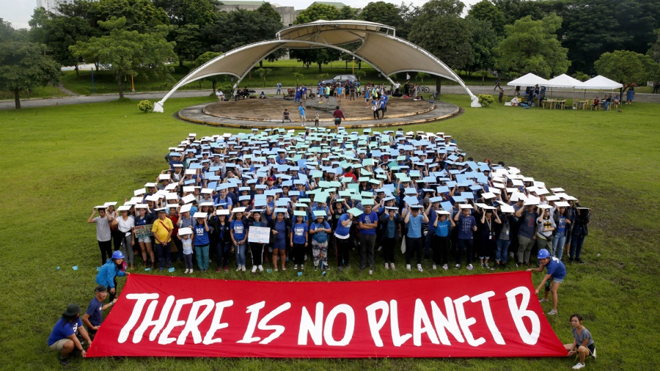 Environmental activists, mostly students, display their message in front of 'a human globe' formation at the University of Philippines campus in Quezon city, Philippines, on Sept. 20, 2019. (Bullit Marquez / AP)