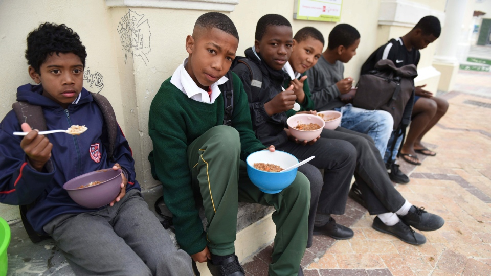 "Children from ""Waves Of Change"" eat a meal supplied by The Lunchbox Fund prior to a surfing lesson in Muizenburg, Cape Town, South Africa, Thursday, Sept. 19, 2019. (AP Photo/Nasief Manie)"