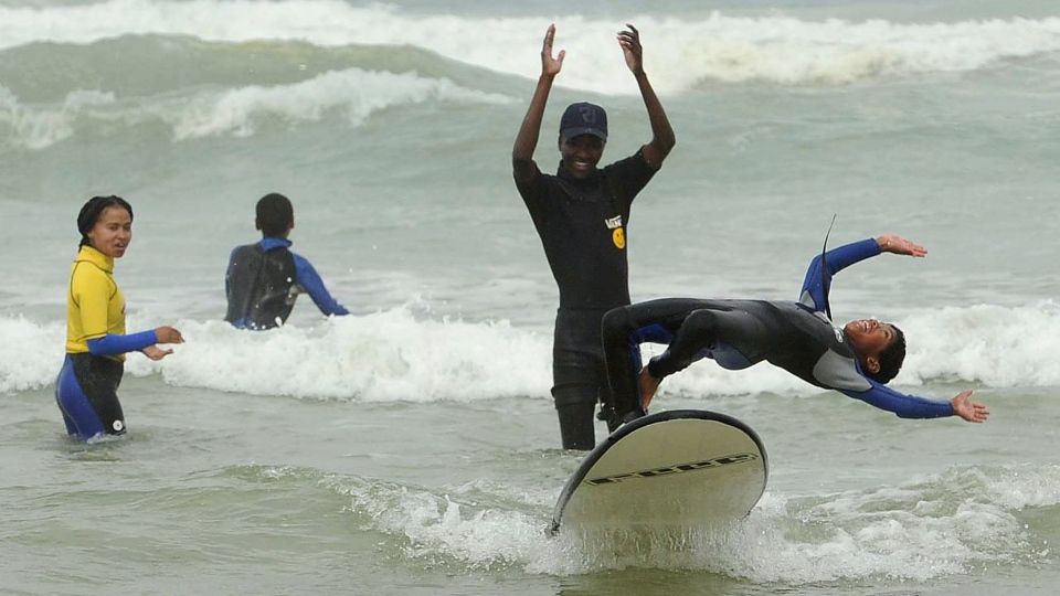 "Children from ""Waves Of Change"" during a surfing lesson in Muizenburg, Cape Town, South Africa, Thursday, Sept. 19, 2019. Prince Harry and his wife, Meghan, along with their infant son, Archie, are making their first official tour to Africa and will visit the project which trains and supports local surf mentors to provide mental health services to young people. (AP Photo/Nasief Manie)"