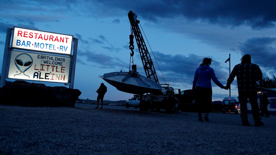"People walk near the Little A'Le'Inn during an event inspired by the ""Storm Area 51"" internet hoax, Thursday, Sept. 19, 2019, in Rachel, Nev. Hundreds have arrived in the desert after a Facebook post inviting people to ""see them aliens"" got widespread attention and gave rise to festivals this week. (AP Photo/John Locher)"