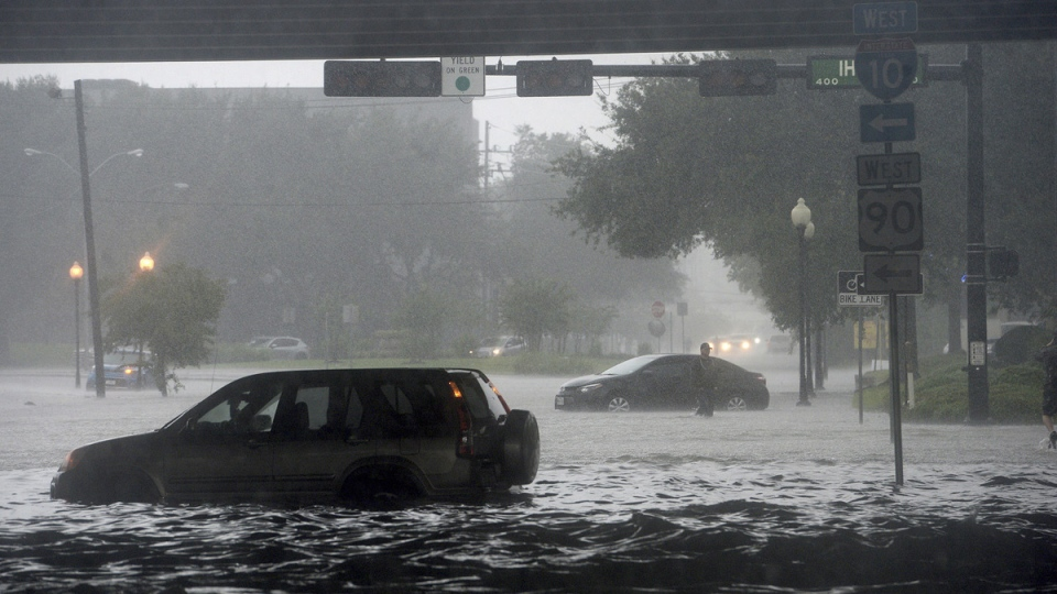 Stalled cars sit among flooded Calder Avenue near I-10 in Beaumont, Texas, on  Sept. 19, 2019. (Kim Brent / The Beaumont Enterprise via AP)