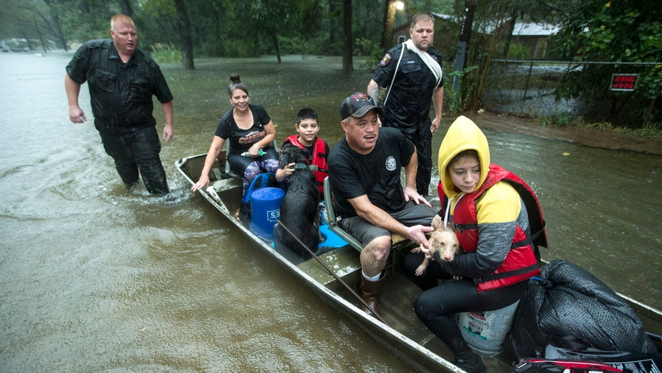 Splendora Police officers Lt. Troy Teller, left, and Cpl. Jacob Rutherford guide a boat carrying Maria, Ramiro, Jr., Ramiro and and Veronica Lopez from their flooded neighborhood inundated by rains from Tropical Depression Imelda inundates the area on Thursday, Sept. 19, 2019, in Spendora, Texas. (Brett Coomer/Houston Chronicle via AP)