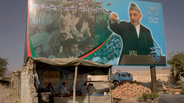 Afghan men take a rest in a shop next to a poster of Afghan President Hamid Karzai in Kabul, Afghanistan, on Saturday, Aug. 29, 2009. (AP / Farzana Wahidy)